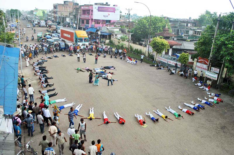 Students and nature lovers lie on the ground to raise awareness for the protection of environment on the main road at Inarwa of Birgunj on Friday, September 23, 2016. Photo: RSS