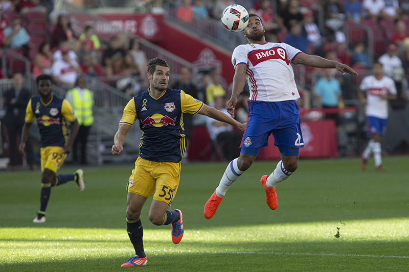 Toronto FC's Jordan Hamilton, right, brings the ball under control in front of New York Red Bulls' Damien Perrinelle during first half of a Major League Soccer match in Toronto, on Sunday, September 18, 2016. Photo: Chris Young/The Canadian Press via AP
