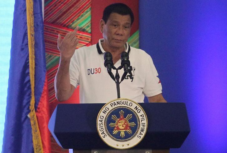Philippine President Rodrigo Duterte raises a middle finger thrust out in an obscene gesture as he speaks before local government officials in Davao city, in southern Philippines, September 20, 2016.   REUTERS/Lean Daval Jr