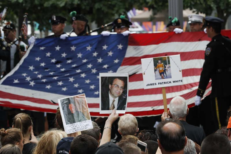 Mourners hold photos of their loved ones during the 15th anniversary of the attacks of the World Trade Center at the National September 11 Memorial, in New York, on Sunday, September 11, 2016. Photo: AP