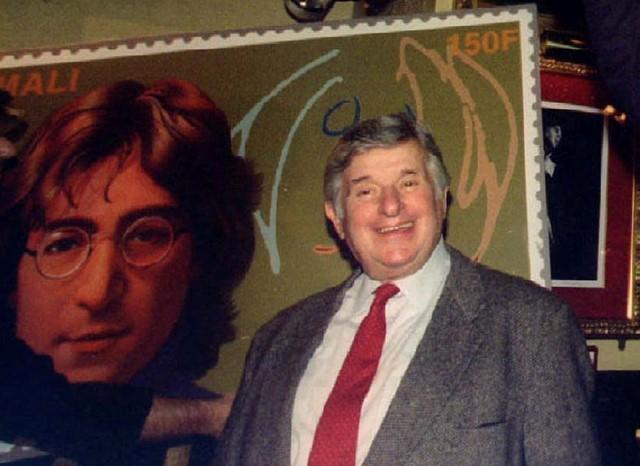 Former Beatles' promoter Sid Bernstein stands with new stamps at a John Lennon World Postal Tribute in New York, New York, December 8, 1995.  REUTERS/Mark Cardwell/File Photo