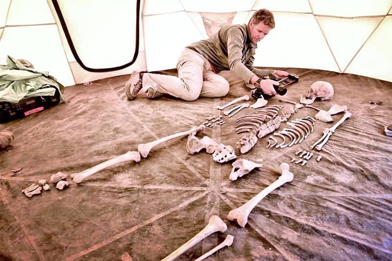 Researcher and producer of the Mountain World Productions Jake Norton taking pictures of a 1,200 years old skeleton of a person, in Samdzong, Mustang, on Monday, August 22, 2016. Jake is filming a one-hour documentary that will air on National Geographic Channel about the first people of the Himalayas. Photo Courtesy: Liesl Clark