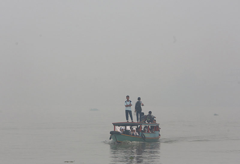 FILE - Students ride on a boat on their way to school while haze from wildfires blanket the Musi River in Palembang, South Sumatra, Indonesia, on Thursday, September 17, 2015. Photo: AP