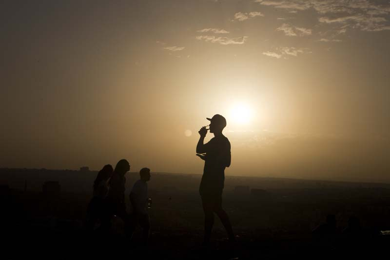 File- A youth takes a drink on a hill overlooking the city after a long hot day in Madrid, Spain, on September 6, 2016. Photo: AP