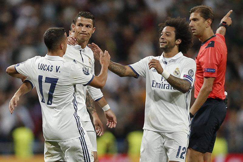 Real Madrid's Lucas Vazquez (left) and Marcelo (second right) congratulate Real Madrid's Cristiano Ronaldo after he scored his side's first goal as referee Paolo Tagliavento (right) awards the goal during a Champions League, Group F soccer match between Real Madrid and Sporting, at the Santiago Bernabeu stadium in Madrid, Spain, on Wednesday, September 14, 2016. Photo: AP