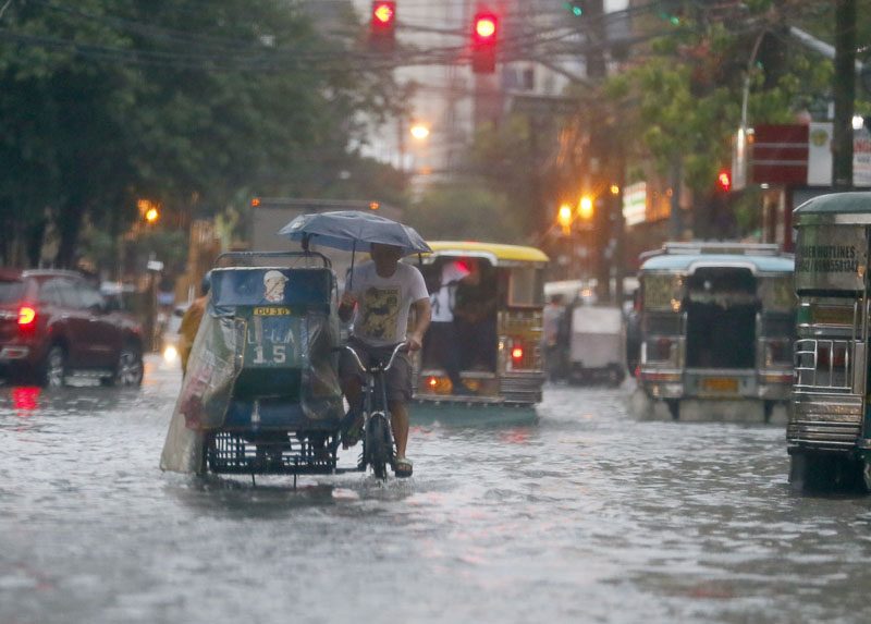 FILE - Commuters and motorists go on their way as heavy monsoon rains inundate low-lying areas in Manila, Philippines, on August 26, 2016. Photo: AP