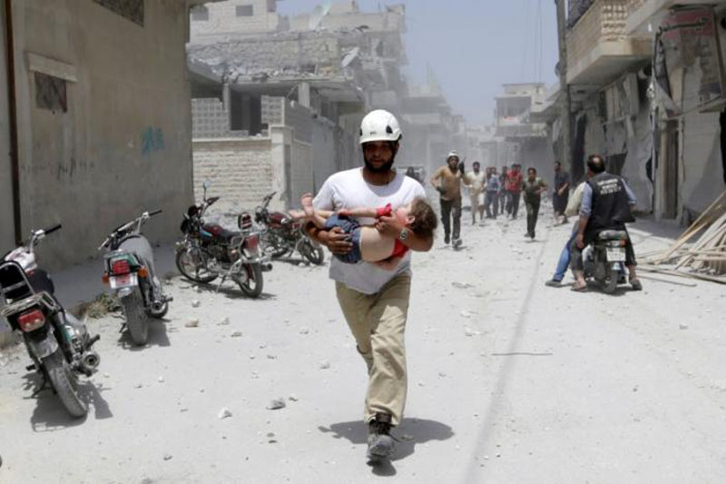 File - A civil defence member carries an injured girl at a site hit by airstrikes in the rebel-controlled area of Maaret al-Numan town in Idlib province, Syria. Photo: Reuters