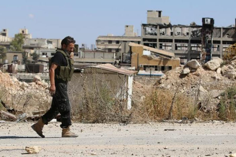 A rebel fighter walks by damaged buildings near Castello road in Aleppo, Syria, on September 16, 2016. Photo: Reuters