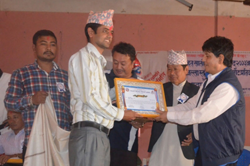 The Himalayan Times' Panchthar correspondent Laxmi Gautam (in Dhaka cap) is honoured by the District Sports Development Committee for his contribution to development of sports in the district, in Phidim, on Friday, September 23, 2016. Photo: THT Online