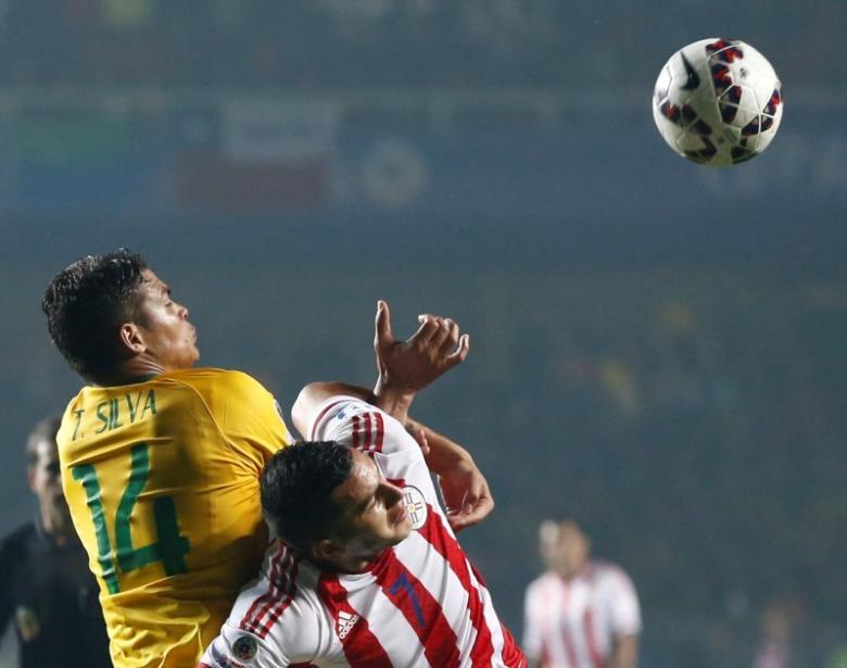 Brazil's Thiago Silva fights Paraguay's Raul Bobadilla for the ball during their Copa America 2015 quarter-finals soccer match at Estadio Municipal Alcaldesa Ester Roa Rebolledo in Concepcion, Chile, June 27, 2015. REUTERS/Mariana Bazo