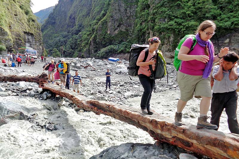Tourists cross a temporary bridge over a stream to reach Beni along the Beni-Jomsom road section in Myagdi district, on Thursday, September 22, 2016. Photo: RSS