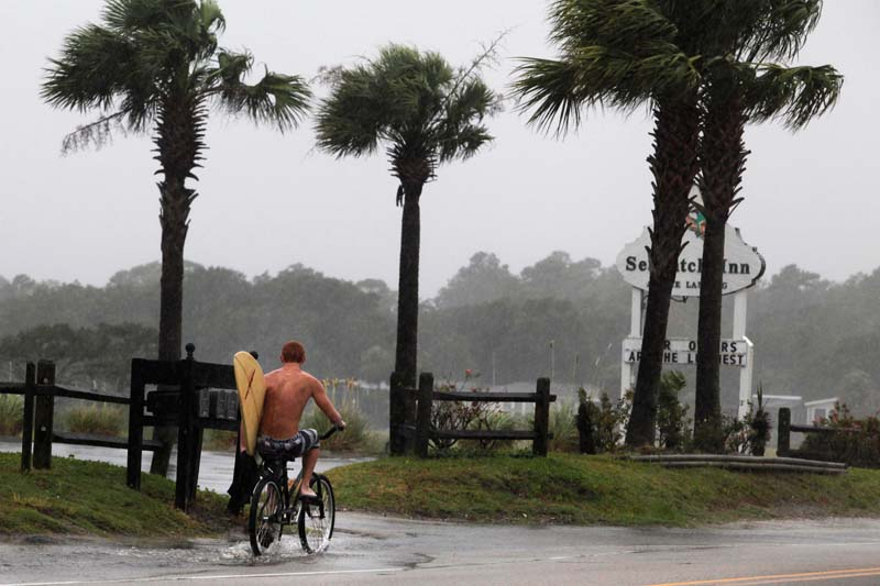A surfer rides his bike down Atlantic Boulevard during the heavy rains of Tropical Storm Hermine as it passed through Garden City Beach, South Carolina, on September 2, 2016. Photo: Reuters