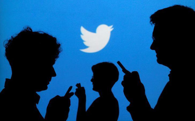 File - People holding mobile phones are silhouetted against a backdrop projected with the Twitter logo in this illustration picture taken in Warsaw on September 27, 2013. Photo: Reuters