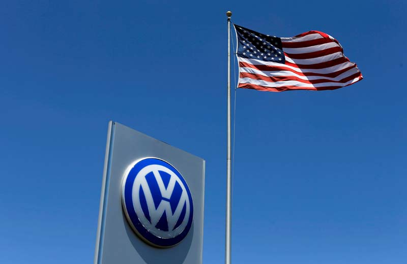 File- A US flag flutters in the wind above a Volkswagen dealership in Carlsbad, California, US, on May 2, 2016. Photo: Reuters