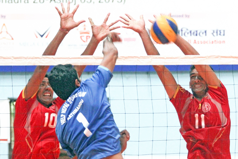 Kul Bahadur Thapa (right) and Dhruba Poudel of Nepal Police Club attempt to block a spike from Help nNepal Sports Club player during their NVA National Womenu0092s and Menu0092s Club Volleyball Championship match at National Sports Council covered hall in Kathmandu on Friday, September 16, 2016. Photo: THT