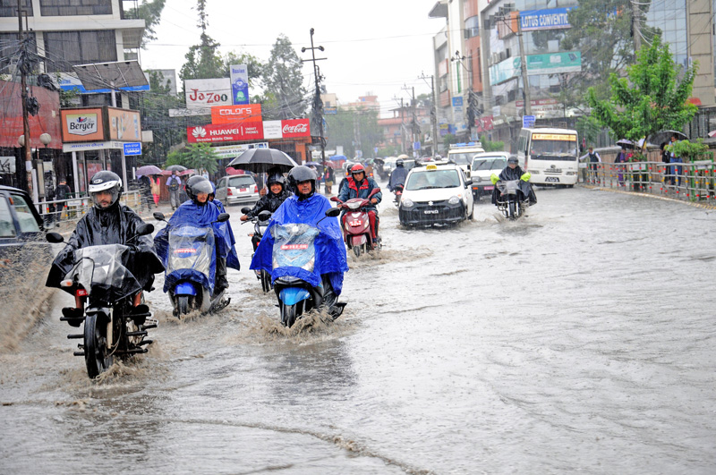 Commuters driving through a waterlogged road after a heavy downpour, in Jawalakhel, Lalitpur, on Monday, September 12, 2016. Photo: THT