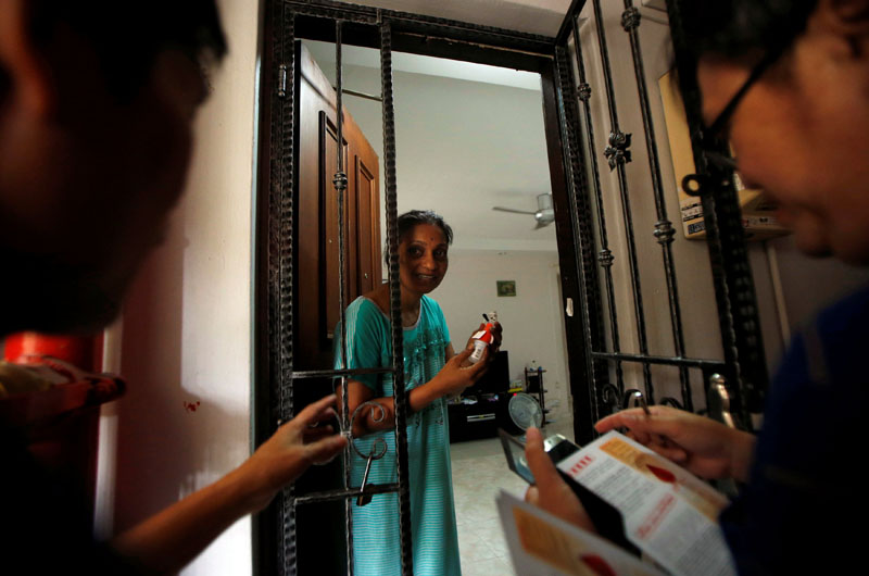 Town council volunteers distribute flyers and insect repellents to residents at a new Zika cluster area in Singapore, on September 1, 2016. Photo: Reuters