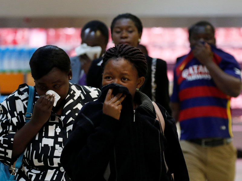 Locals cover their faces during a protest by opposition youths who were demonstrating against alleged brutality by security agents in the capital Harare, Zimbabwe, on August 24, 2016. Photo: Reuters