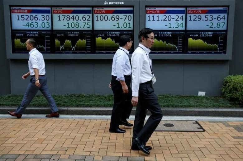 Passersby walk past in front of electronic boards showing Japan's Nikkei share average (L), the Japanese yen's exchange rate against the U.S. dollar (C), British pound (R) and Euro (2nd R) outside a brokerage in Tokyo, Japan, July 6, 2016. REUTERS/Issei Kato - RTX2JVPG