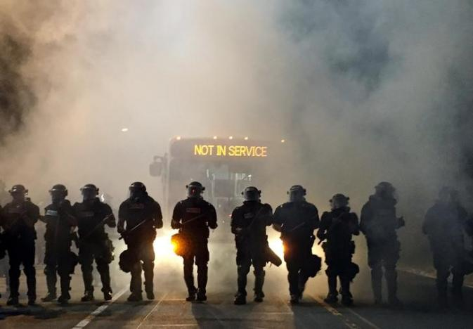 Police officers wearing riot gear block a road during protests after police fatally shot Keith Lamont Scott in the parking lot of an apartment complex in Charlotte, North Carolina, U.S. September 20, 2016. REUTERS/Adam Rhew/Charlotte Magazine