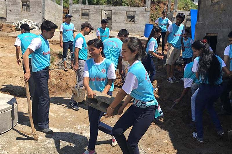 Students and teachers of the Samakhusi-based Supreme College work to build a sample community under the Dhurmus-Suntali Foundation at Giranchaur of Sindhupalchok district, on Thursday, September 22, 2016. Photo: RSS