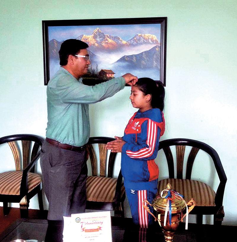 NOC President Jeevan Ram Shrestha felicitating taekwondo player Melisa Khadgi in Lalitpur on Sunday.