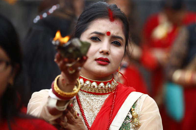 A woman holding an oil lamp as she offers prayers during Teej festival on the premises of Pashupatinath temple, in Kathmandu, on Sunday, September 4, 2016. Photo: THT