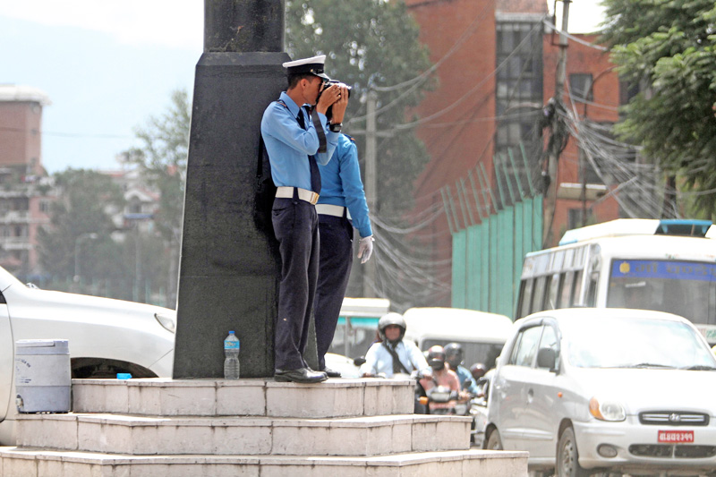 A traffic policeman holding a camera to shoot ntraffic rule violations, in Kathmandu, on Thursday, September 22, 2016. Photo: THT