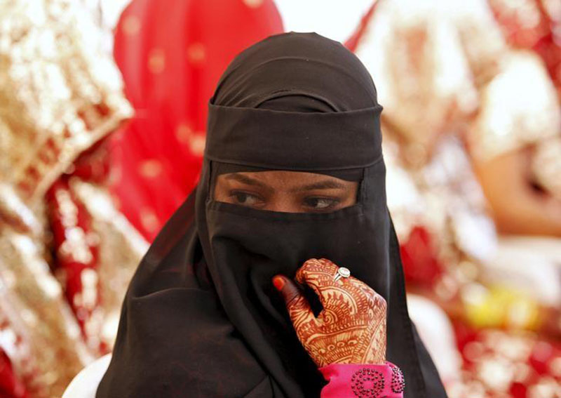 A veiled Muslim bride waits for the start of a mass marriage ceremony in Ahmedabad, India, on October 11, 2015.  Photo: Reuters