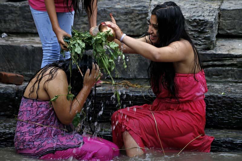 Women perform a ritual bath during Rishi Panchami festival on the bank of the Bagmati River at the Pashupathinath Temple premises, a UNESCO World Heritage Site in Kathmandu, on Tuesday, September 6, 2016. Photo: Skanda Gautam/ THT