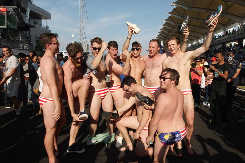 Australian men celebrate in Budgy Smuggler-brand swimsuits decorated with the Malaysian flag at the conclusion of the Malaysian Formula One Grand Prix in Sepang, Malaysia, on Sunday, October 2, 2016. Photo: AP