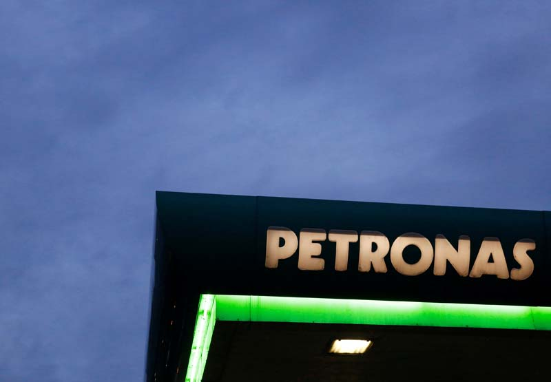 A logo of a Petronas fuel station is seen against a darkening sky in Kuala Lumpur, Malaysia, on February 10, 2016. Photo: Reuters