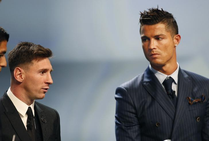 Barcelona's Lionel Messi (L) looks at Cristiano Ronaldo (R) during he Best Player UEFA 2015 Award ceremony during the draw ceremony for the 2015/2016 Champions League Cup soccer competition at Monaco's Grimaldi Forum in Monte Carlo August 27, 2015.  REUTERS/Eric Gaillard
