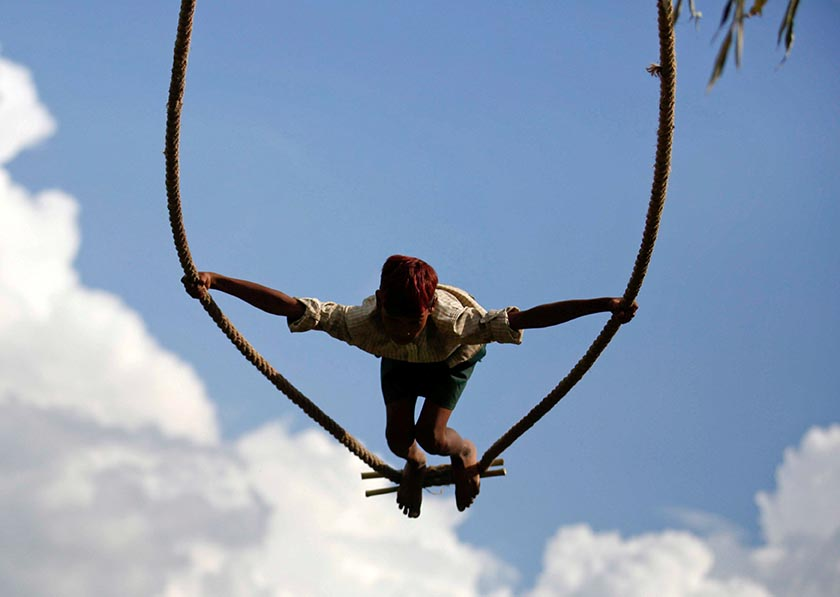 A boy plays on a traditional swing during Dashain, the biggest religious festival for Hindus in Nepal, in Kathmandu, Nepal October 4, 2016. Photo: Reuters