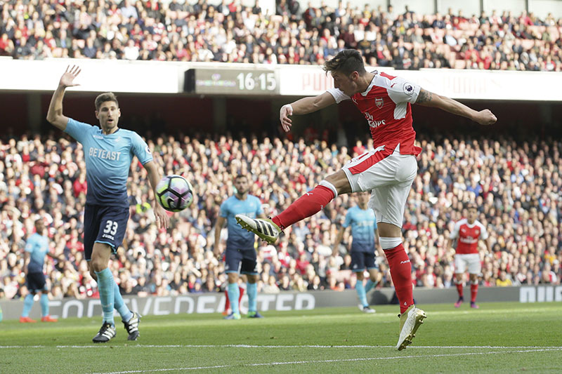 Arsenal's Mesut Ozil (right) scores a goal during the English Premier League football match between Arsenal and Swansea City at The Emirates Stadium in London, on Saturday, October 15, 2016. Photo: AP