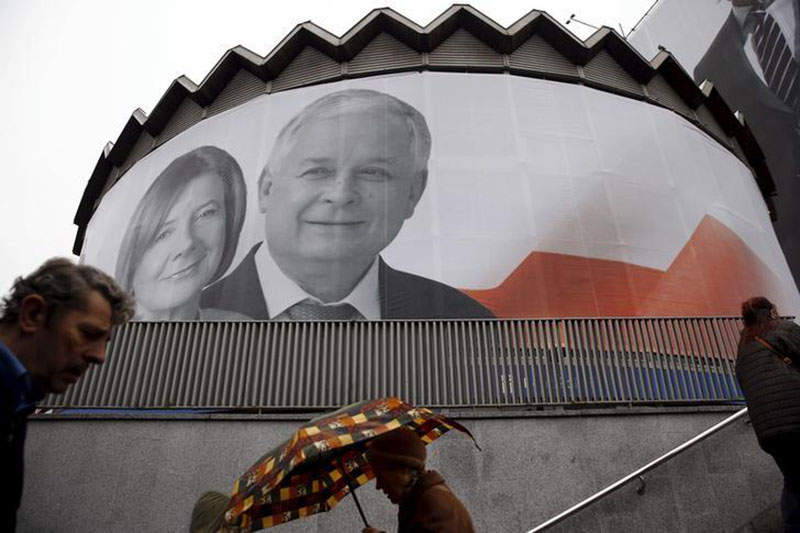 People walk past a giant picture of late Polish president Lech Kaczynski and his wife Maria, who died six years ago when a Polish government plane crashed in Smolensk, Russia, hanging on a building in the centre of Warsaw, Poland, on April 10, 2016. Photo: Reuters