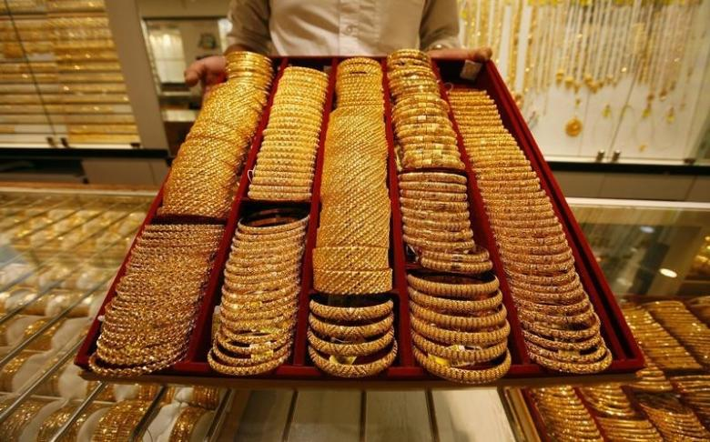 A salesman displays a tray of gold bangles for the camera at a jewellery shop in Singapore October 7, 2009.  REUTERS/Vivek Prakash