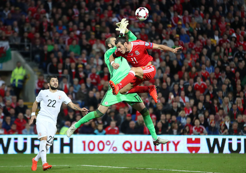 Wales' Gareth Bale (right) and Georgia goalkeeper Giorgi Loria battle for the ball during the 2018 World Cup qualifying, group D soccer match, Wales versus Georgia at the Cardiff City Stadium, Cardiff, Wales, on Sunday October 9, 2016. Photo: Nick Potts/PA via AP