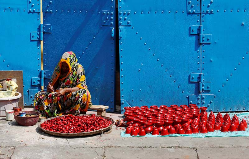 A woman paints earthen lamps which are used to decorate temples and homes during Diwali, the Hindu festival of lights, in Kolkata, India, on Monday, October 17, 2016. Photo: Reuters