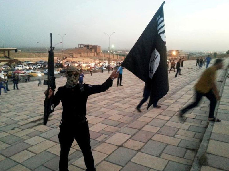 File - A fighter of the Islamic State of Iraq and the Levant (ISIL) holds an ISIL flag and a weapon on a street in the city of Mosul, Iraq, on June 23, 2014. Photo: Reuters