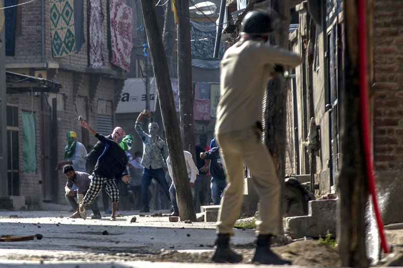 Kashmiri protesters throw stones and bricks at an Indian policeman as he prepares to fire pallet gun during a protest in Srinagar, Indian controlled Kashmir, on Friday, October 7, 2016. Photo: AP