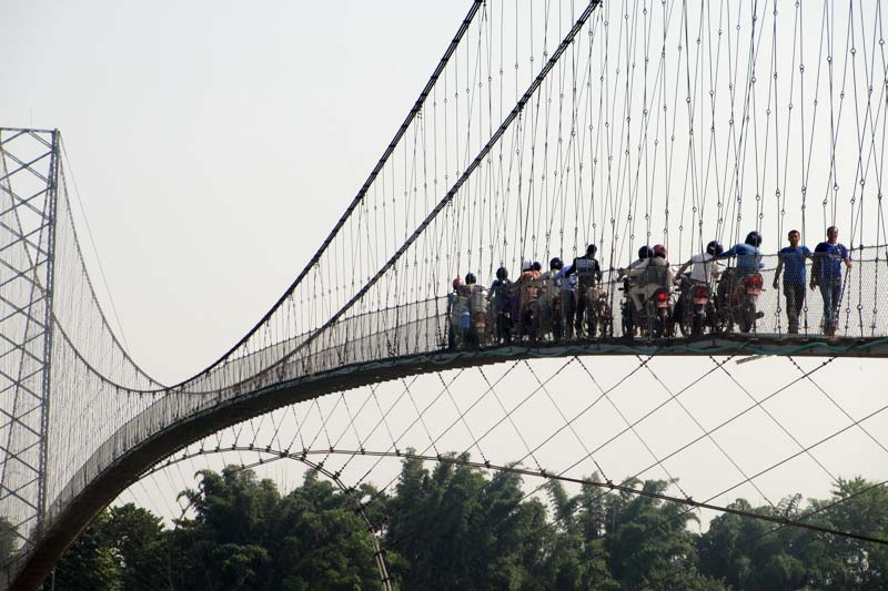 Locals of Kanchanpur district cross a suspension bridge over the Mahakali River, on Monday, October 24, 2016. Photo: RSS