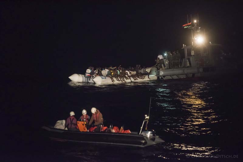 Refugees sit in a inflatable boat, background left,  while a speedboat, labelled as Libyan Coast Guard, background right, and Sea-Watch members in a boat foreground arrive off the Libyan coast  in the Mediterranean Sea, on October 21, 2016. Photo: AP