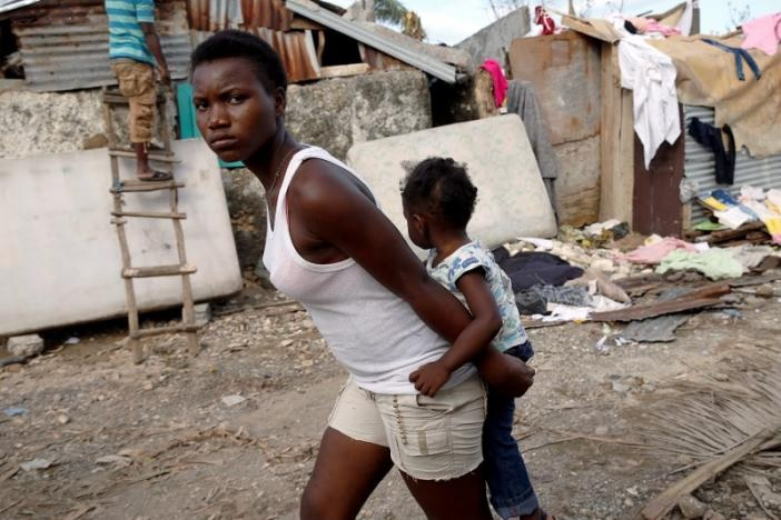 A woman carries chile as they walk in front of destroyed houses after Hurricane Matthew passes Jeremie, Haiti on October 7, 2016. Photo: Reuters