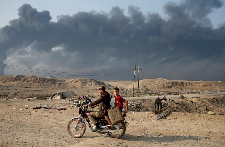 Armed members of Shi'ite militia Hashid Shaabi ride a motorbike near Qayyara, south of Mosul, Iraq October 27, 2016. Smoke in the background is from burning oilfields set ablazed by Islamic State fighters. REUTERS/Goran Tomasevic