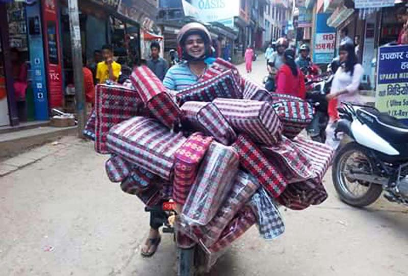 A vendor poses on his motorbike while he takes Dhaka bags to the market in Palpa district, on Monday, October 3, 2016. Palpali Dhaka fabric is popular among customers across Nepal.
