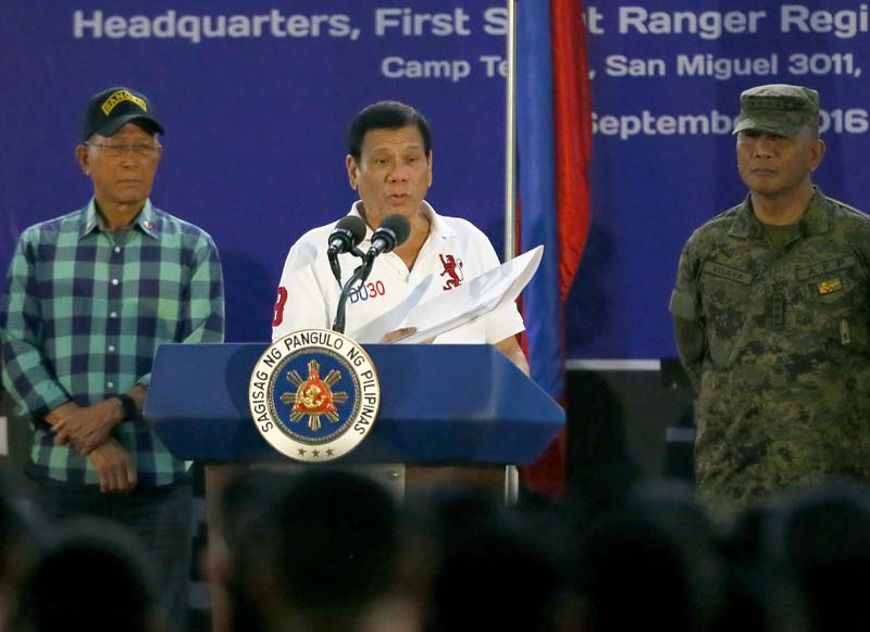 File- Philippine President Rodrigo Duterte holds a folder containing the names of Philippine politicians and government officials allegedly involved in illegal drugs during his visit to the headquarters of the Philippine Army Scout Rangers at Camp Tecson in San Miguel township, north of Manila, Philippines, on September 15, 2016. Photo: AP