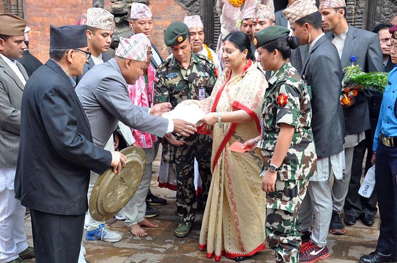 President Bidya Devi Bhandari receives five-cloloured thread and citron as prasad from the leader of  devgans (staff) of Navadurga Temple Viku Lal Banmala in Bhaktapur on the occasion of Kojagrat Purnima, on Saturday, October 15, 2016. Photo: RSS