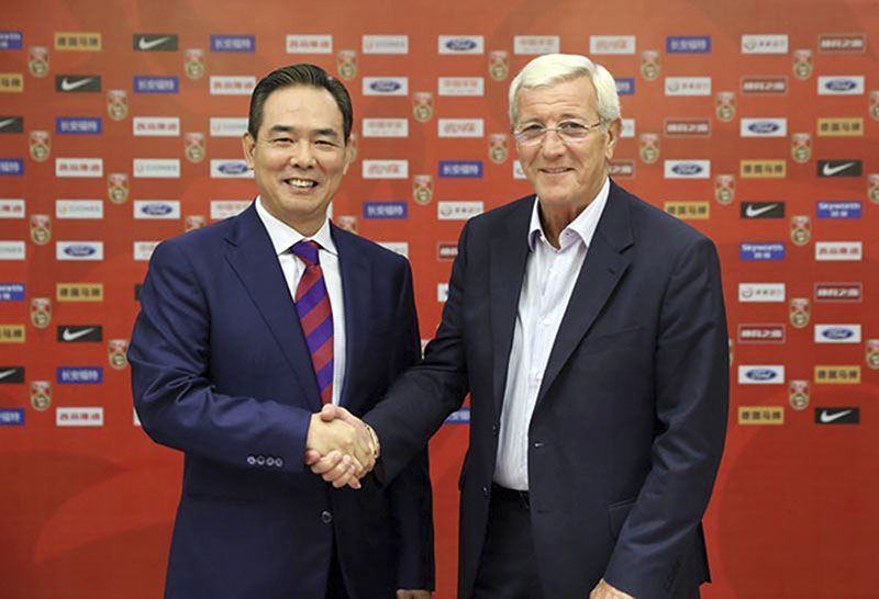 World Cup-winning manager Marcello Lippi (right) shakes hands with president of the Chinese Football Association, Cai Zhenhua during a ceremony in Guangzhou in southern China's Guangdong province, on Saturday, October 22, 2016. Photo: Chinese Football Association via AP