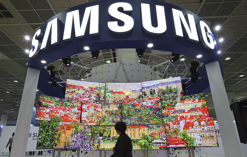 A visitor walks by Samsung Electronics TV screens at Korea Electronics Show or KES in Seoul, South Korea, on October 26, 2016. Photo: AP